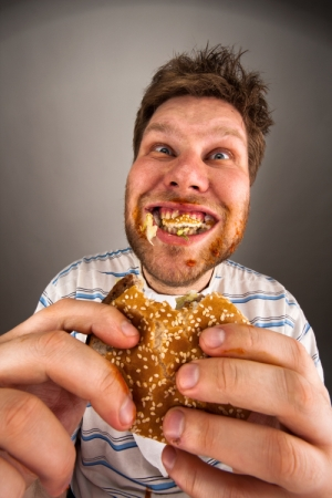 a man eating a burger in a messy way