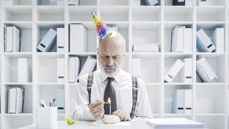 a business man lighting the candle of his birthday cake on his own and in the office